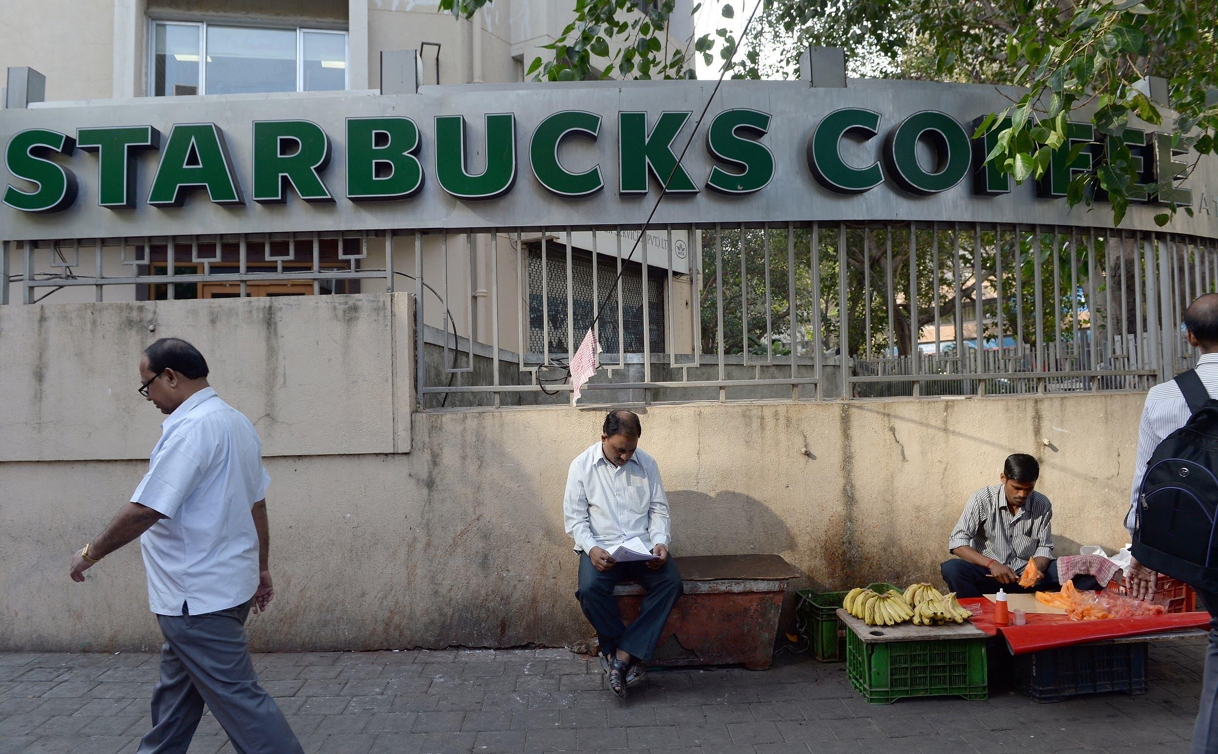 Indian pedestrians walk past a Starbucks Coffee shop in Mumbai on January 15, 2016. (AFP)