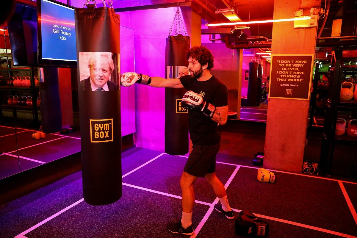A gym instructor punches a boxing bag containing an image of Britain's former Foreign Secretary Boris Johnson during a Brexfit gym class at Gym Box in London, Britain. (Reuters)