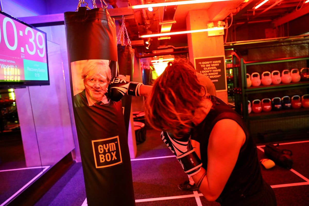 A gym member punches a boxing bag containing an image of Britain's former Foreign Secretary Boris Johnson during a Brexfit gym class at Gym Box in London, Britain. (Reuters)