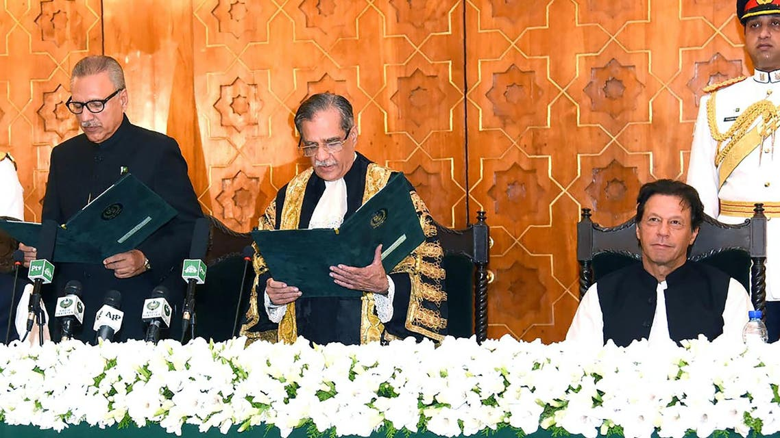 Pakistan Prime Minister Imran Khan (R) witnesses while Chief Justice of Pakistan Mian Saqib Nisar (C) takes oath from President Arif Alvi (L) in Islamabad on September 9, 2018. (AFP)
