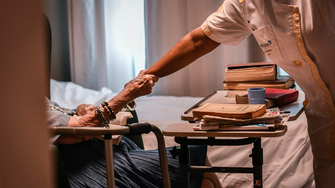 An elderly resident holds the forearm of a nurse on July 5, 2018, in an establishment of accommodation for dependent elderly (EHPAD) in Paris.