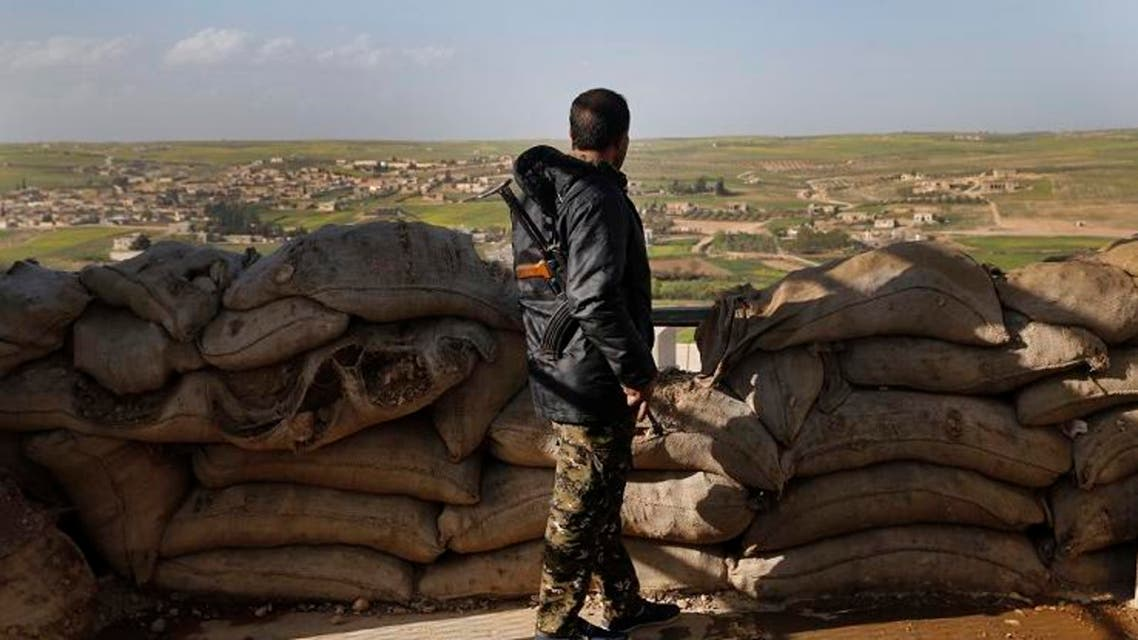 A fighter from the US-backed Syrian Manbij Military Council stands behind a sandbags barrier as he looks toward Turkish-backed fighter's position. (File photo: AP)
