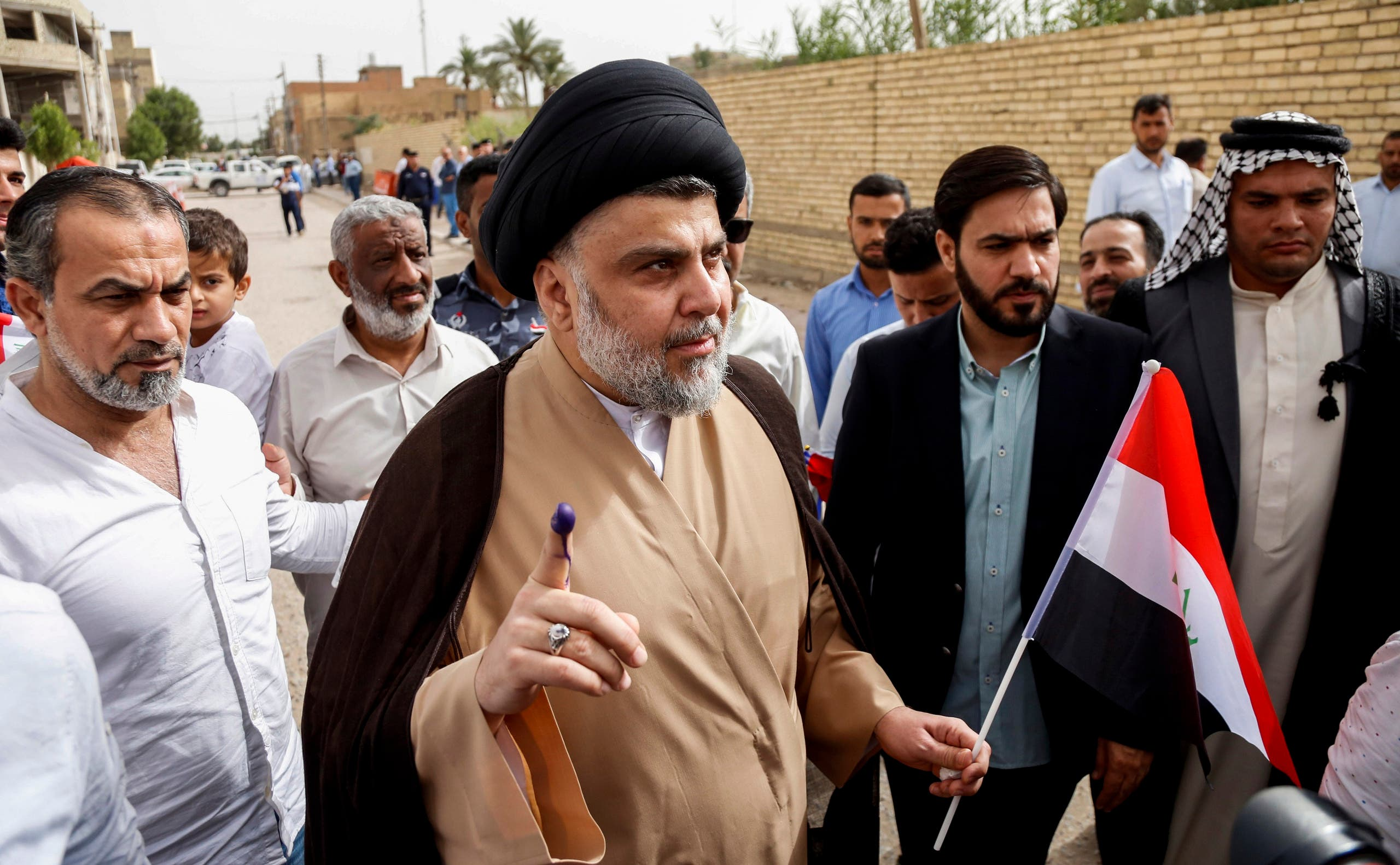 Moqtada al-Sadr shows his ink-stained index finger outside a polling station in Najaf on May 12, 2018 as the country votes in the first parliamentary election since declaring victory over ISIS. (AFP)