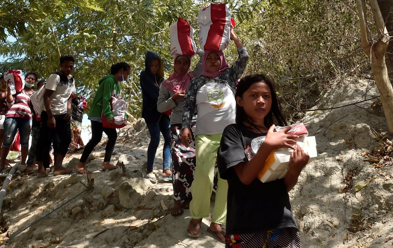 Residents affected by earthquake and tsunami carry aid provided during the visit of Indonesian President Joko Widodo in Central Sulawesi on October 3, 2018. (Reuters)