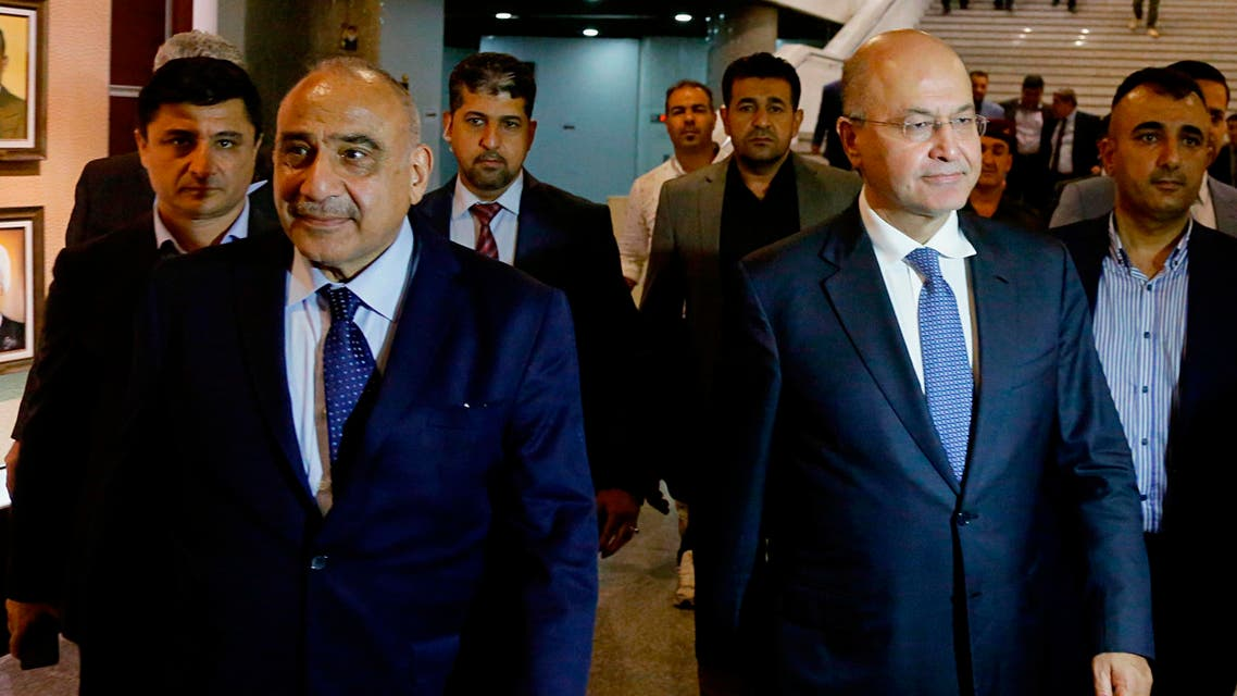 Iraq's new President Barham Salih, center right, walks with new Prime Minister Adel Abdul-Mahdi, center left, in the parliament building in Baghdad, Iraq, Tuesday, Oct. 2, 2018. (AP)