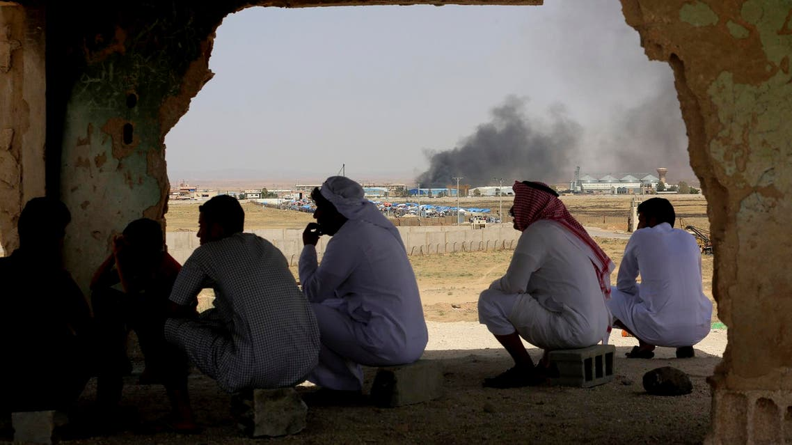 Jordanians watch aid deliveries to Syrians fleeing government offensive in the south as smoke from unknown fire rises on July 3, 2018. (File photo: AP)