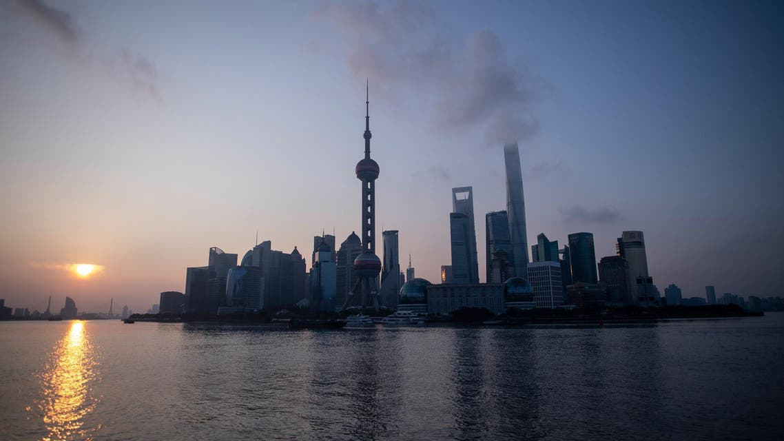 The sun rises behind the skyline of Shanghai in the Lujiazui Financial District of Pudong on August 8, 2018. (AFP)