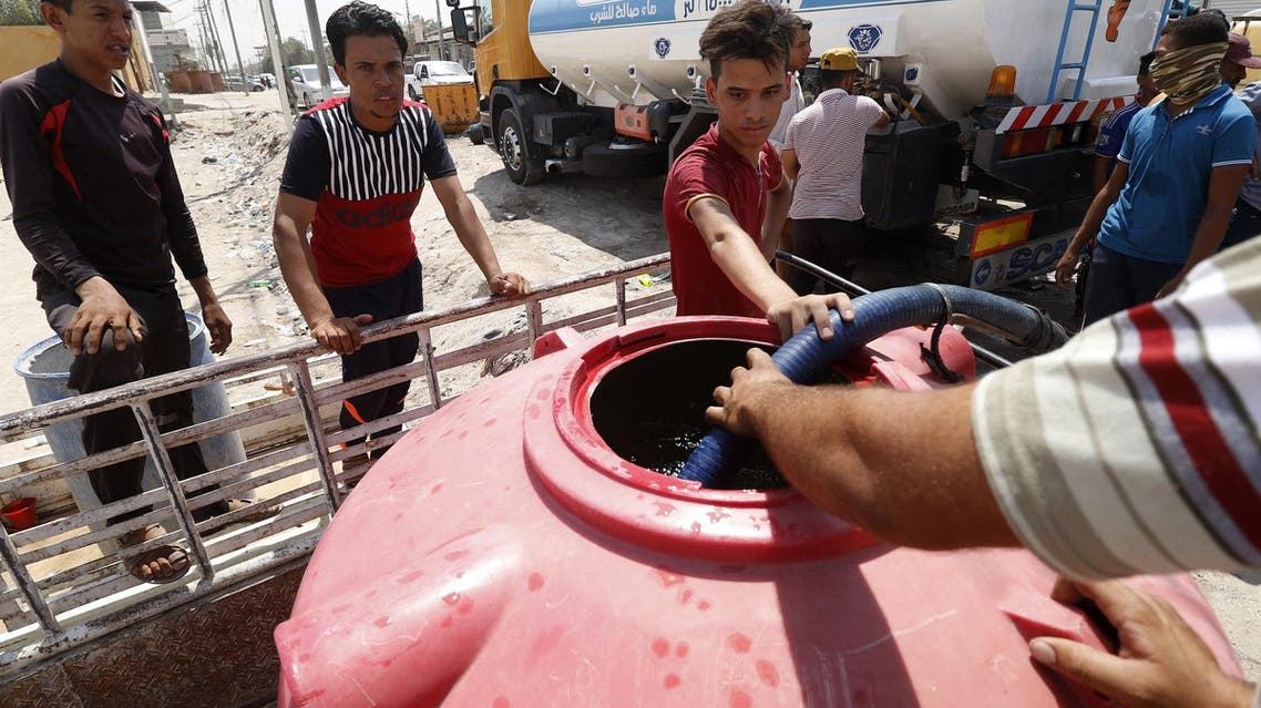 Iraqi youths fill up water tanks in Abu al-Khasib, southeast of Basra, on August 31, 2018. (AFP)