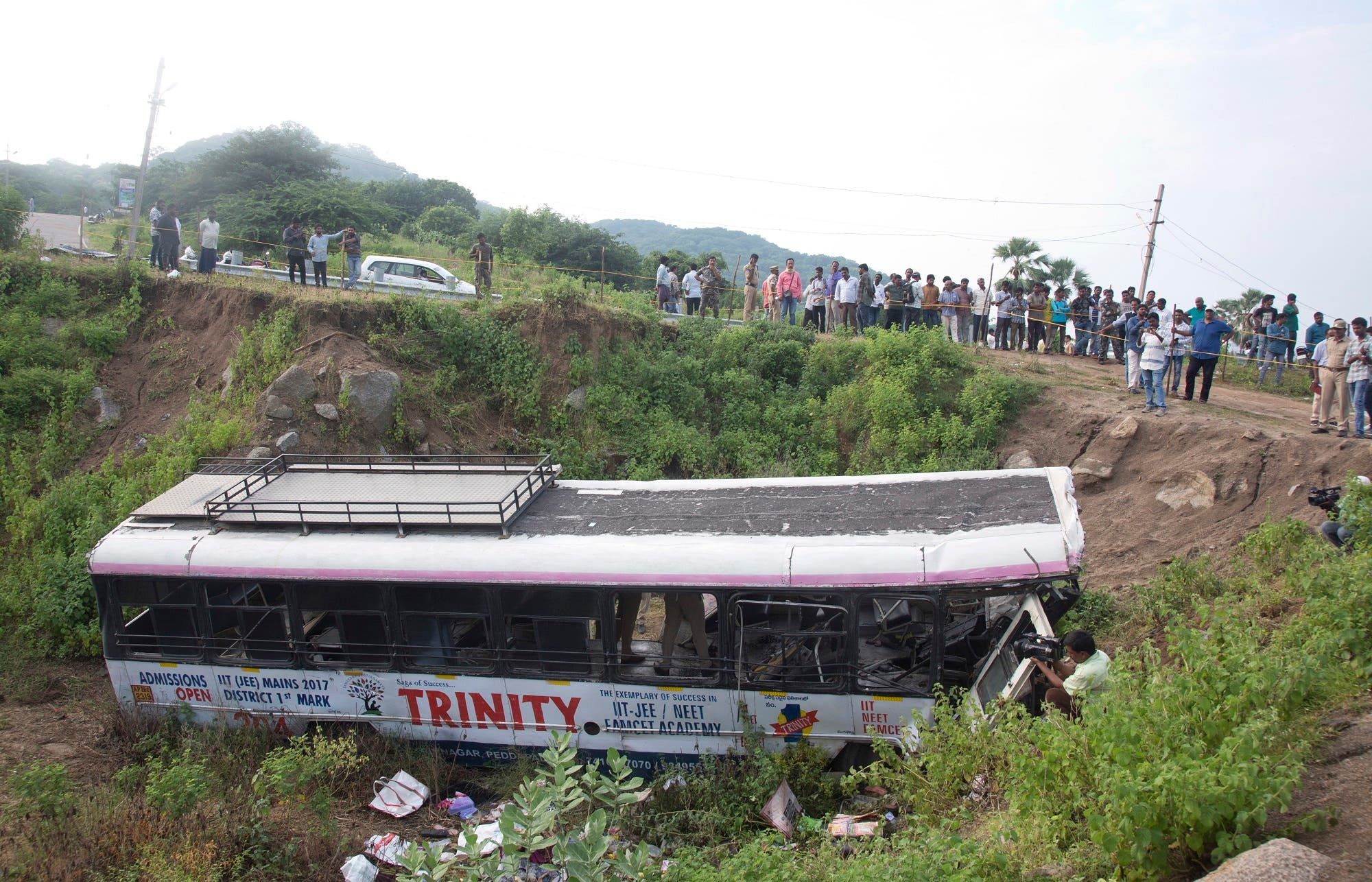 A crowd gathers around a bus that fell into a gorge in Jagtiyal district, in Telangana, on Sept. 12, 2018. (AP)
