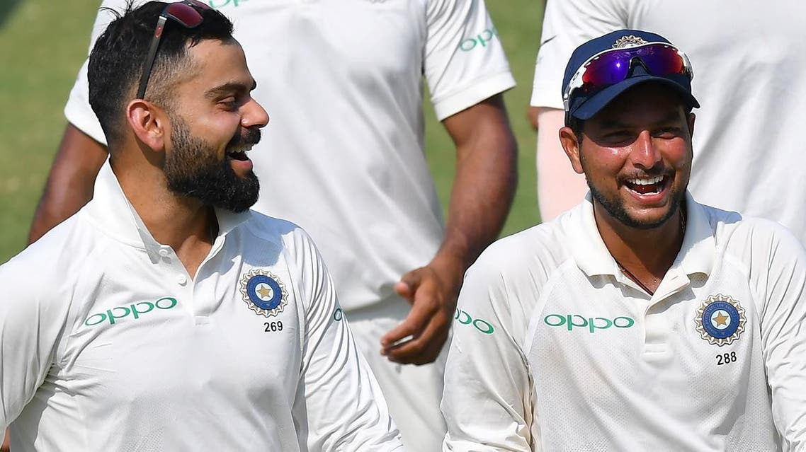 Indian captain Virat Kohli along with teammate Kuldeep Yadav laugh as they walk back after winning the first Test cricket match between India and West Indies in Rajkot on October 6, 2018.  (AFP)