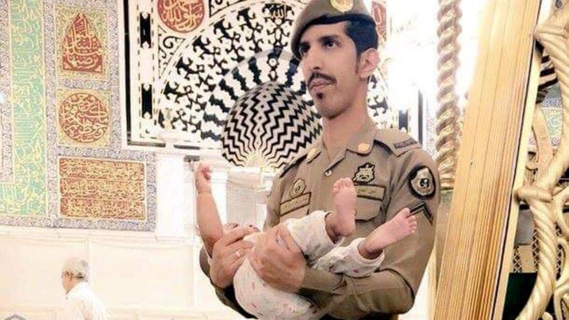 In a scene that took place at the Prophet's Mosque in Madinah, the security man was captured on camera whilst holding the child. (Supplied)