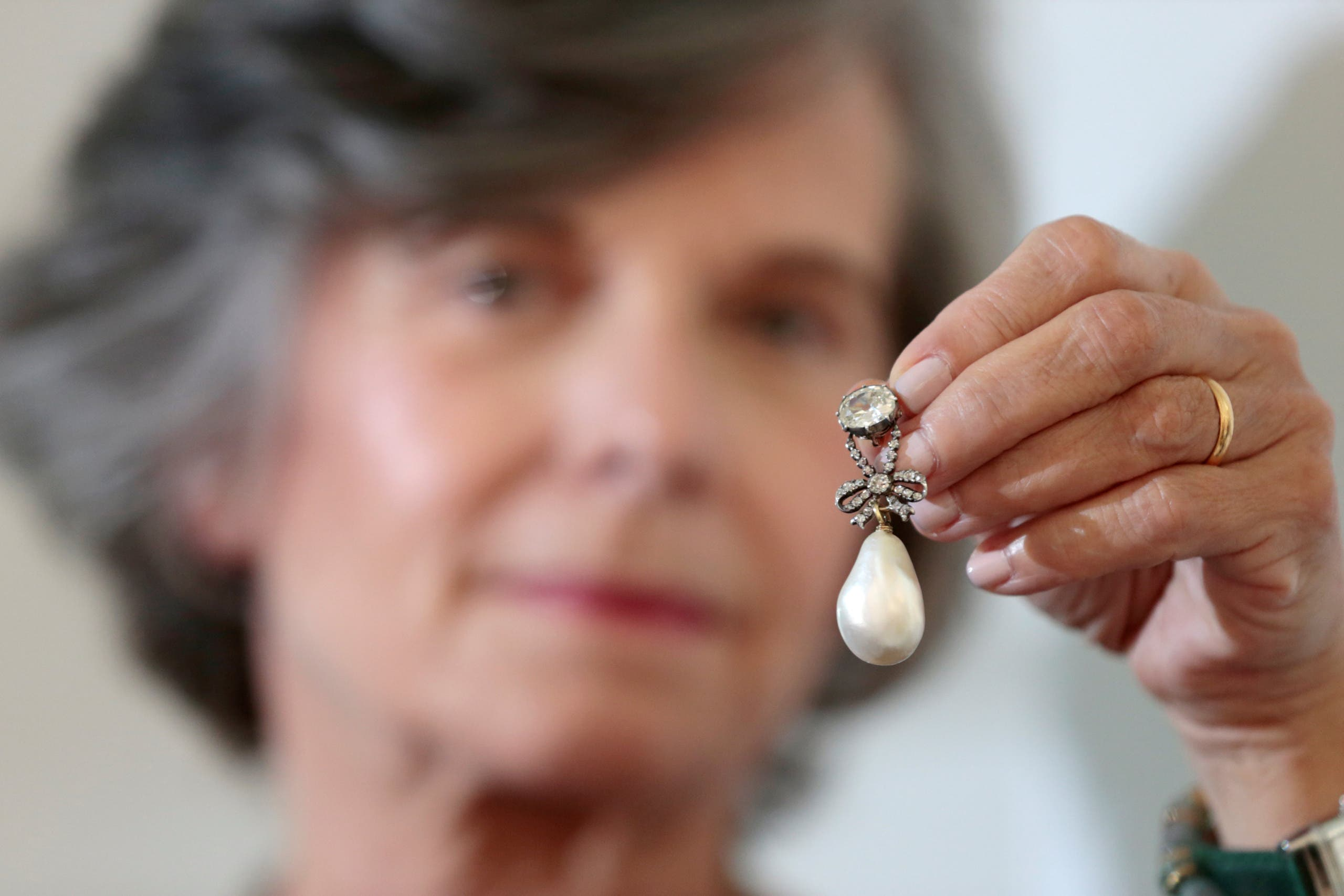 A member of Sotheby's staff holds a pearl and diamond pendant once belonging to Queen Marie Antoinette of France on display at Sotheby's in Dubai on October 9, 2018. (Reuters)