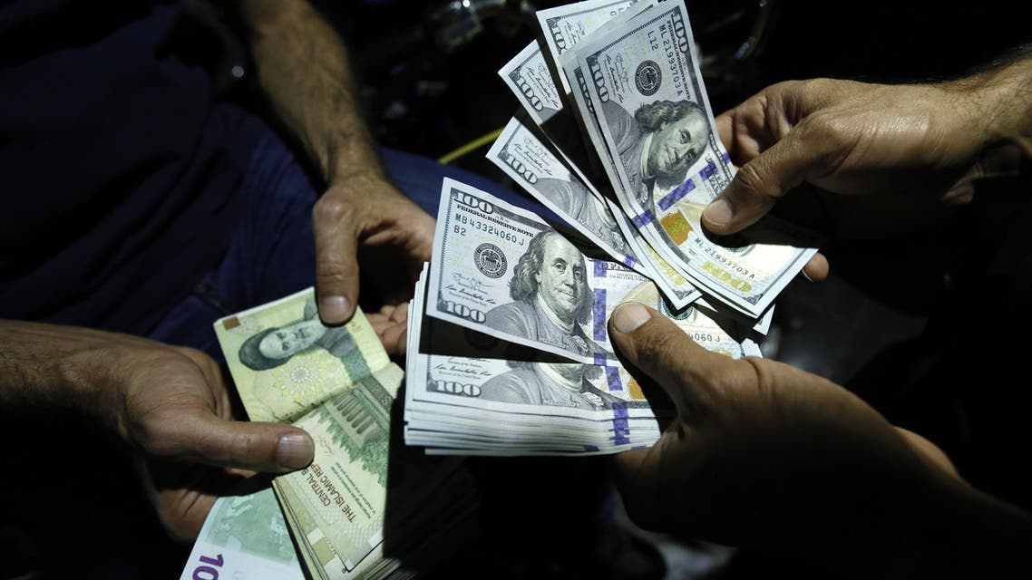 """A man exchanges Iranian Rials against US Dollars at an exchange shop in the Iranian capital Tehran on August 8, 2018. US President Donald Trump warned the world the previous day against doing business with Iran as Washington reimposed """"the most biting sanctions ever"""" on the Islamic republic, triggering a mix of anger, fear and defiance in Tehran."""