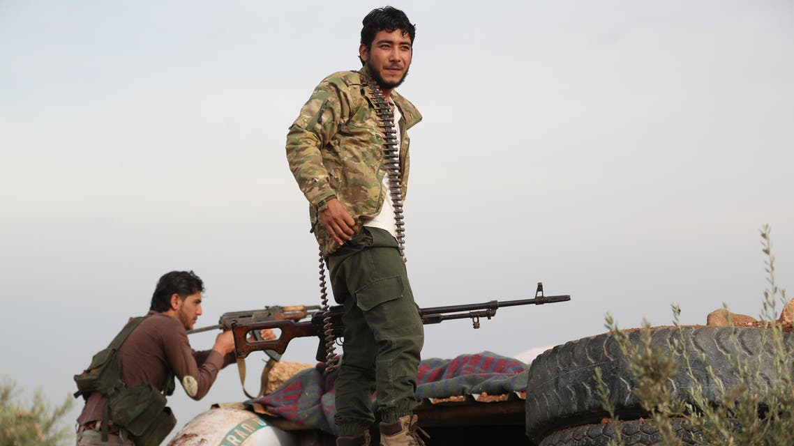 A Syrian rebel-fighter from the National Liberation Front (NLF) gather on the frontline with regime forces inside the demilitarised zone, in the south east of Idlib province on October 9, 2018. Jihadist factions including Syria's former Al-Qaeda branch have withdrawn heavy weapons from parts of a planned buffer zone in Idlib province, a monitor said on October 9, two days ahead of a deadline. The U-shaped buffer, agreed by regime ally Russia and rebel-backer Turkey, will separate opposition and government forces and is meant to be free of both heavy weapons and jihadists by October 15.
