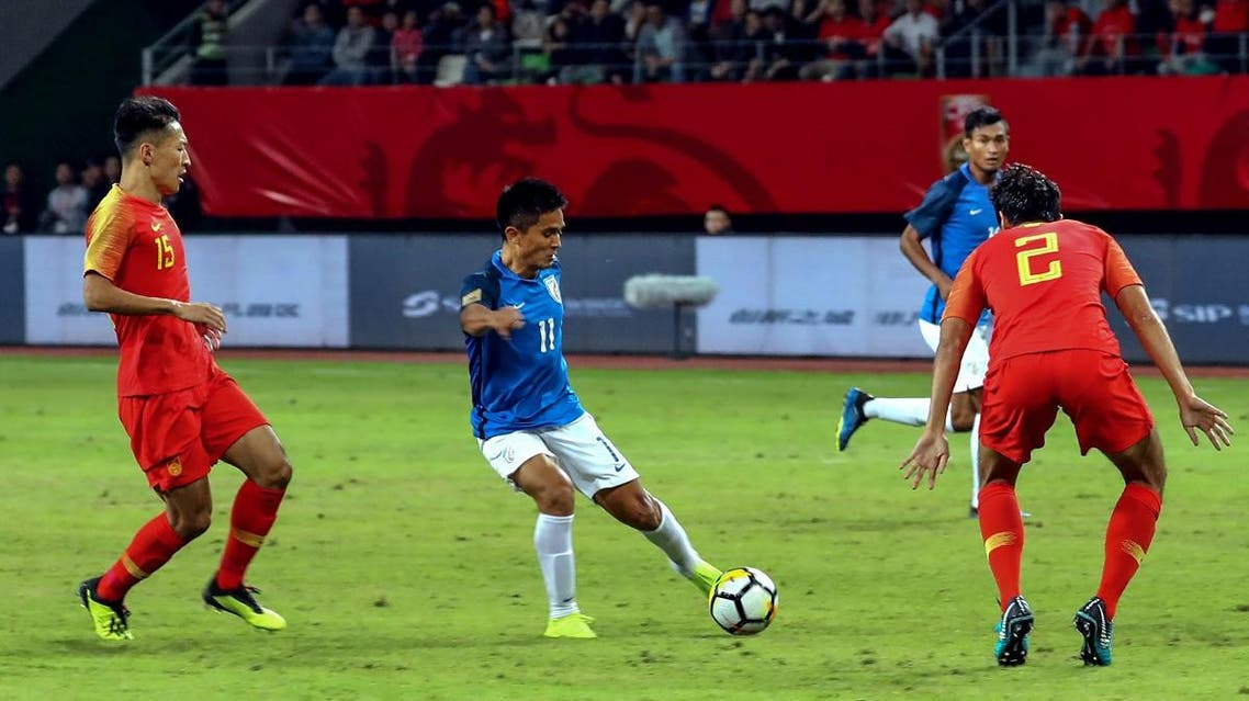 India's Sunil Chettri (C) kicks the ball past China's Liu Yiming (R) during an international friendly football match between China and India in Suzhou in China's eastern Jiangsu province on October 13, 2018.  (AFP)