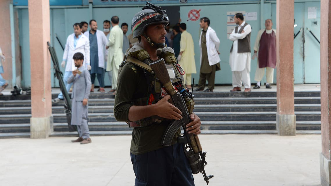 An Afghan policeman stands as unseen volunteers carry an injured on a stretcher to a hospital, following an attack that targeted a parliamentary election rally in the Kama district of the eastern province of Nangarhar, in Jalalabad on October 2, 2018. At least 13 people were killed in a suicide attack on an Afghan election campaign rally on October 2, officials said, in the latest violence ahead of this month's legislative vote. The attack is the first suicide assault since campaigning officially kicked off last Friday for the parliamentary elections, preparations for which have already been marred by bloody violence.