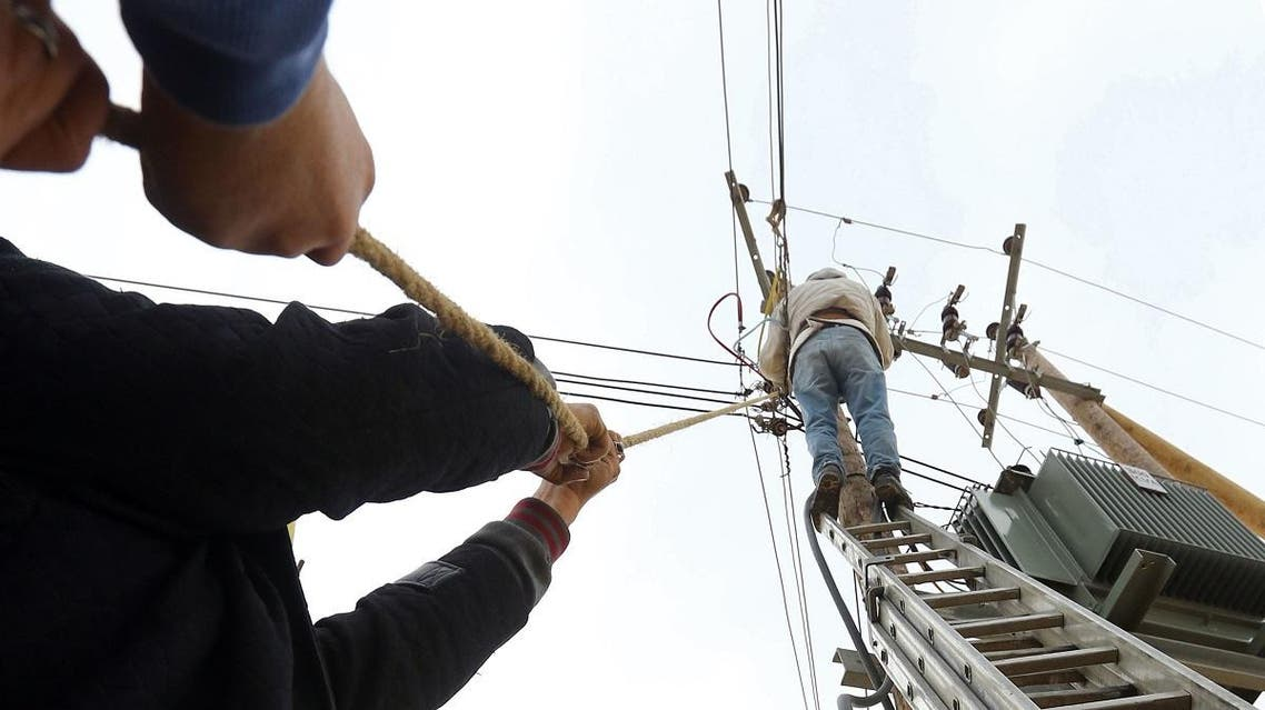 Employees of the General Electric Company fix cables in the Libyan capital, Tripoli, on January 19, 2017. (AFP)