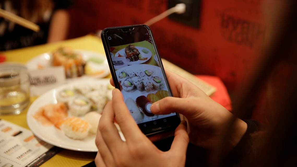 Customer Chiara Valenzano takes pictures of her dishes as she has lunch at the 'This is not a Sushi bar' restaurant, in Milan, Italy. (AP)