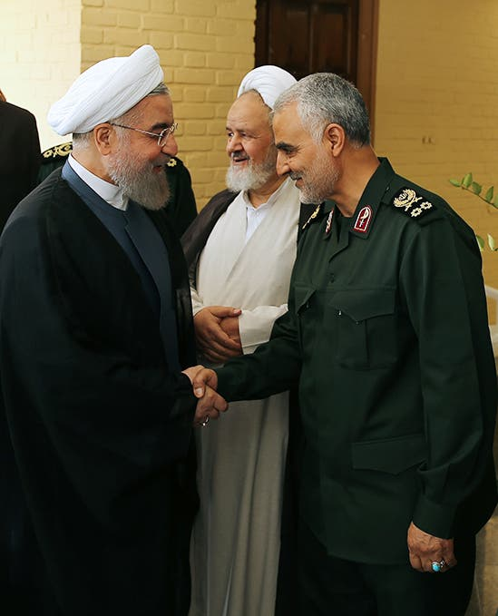 A handout picture provided by the office of Iranian President Hassan Rouhani shows him (L) shaking hands with Gen. Qassem Suleimani, in Tehran on September 15, 2015. (AFP)