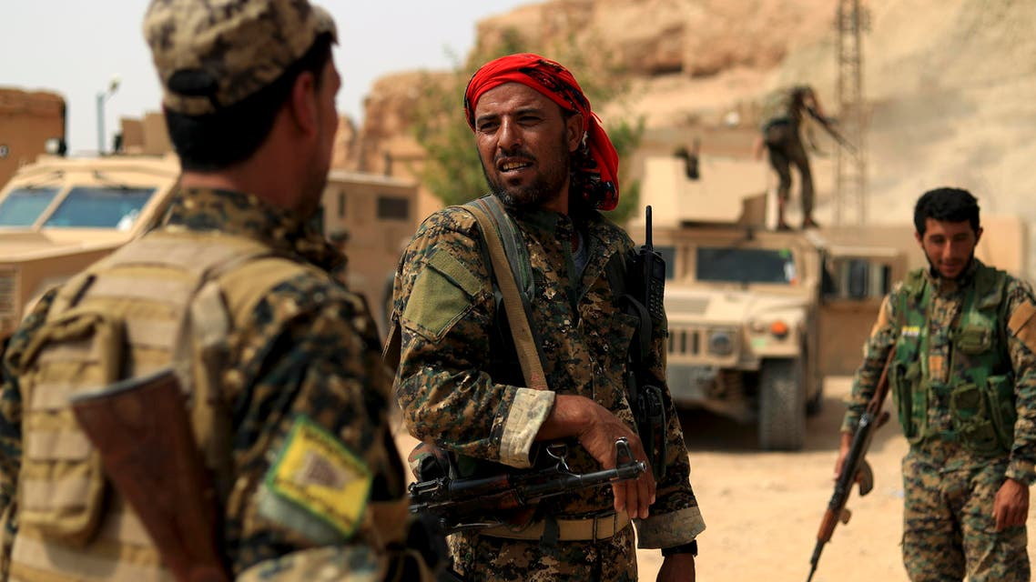 """Members of the Syrian Democratic Forces (SDF) gather in the village of Susah in the eastern province of Deir Ezzor, near the Syrian border with Iraq on September 13, 2018. US-backed fighters are fighting in Deir Ezzor to oust Islamic State jihadists from the town of Hajin on the east bank of the Euphrates, the most significant remnant of the sprawling """"caliphate"""" the jihadists once controlled spanning Syria and Iraq."""