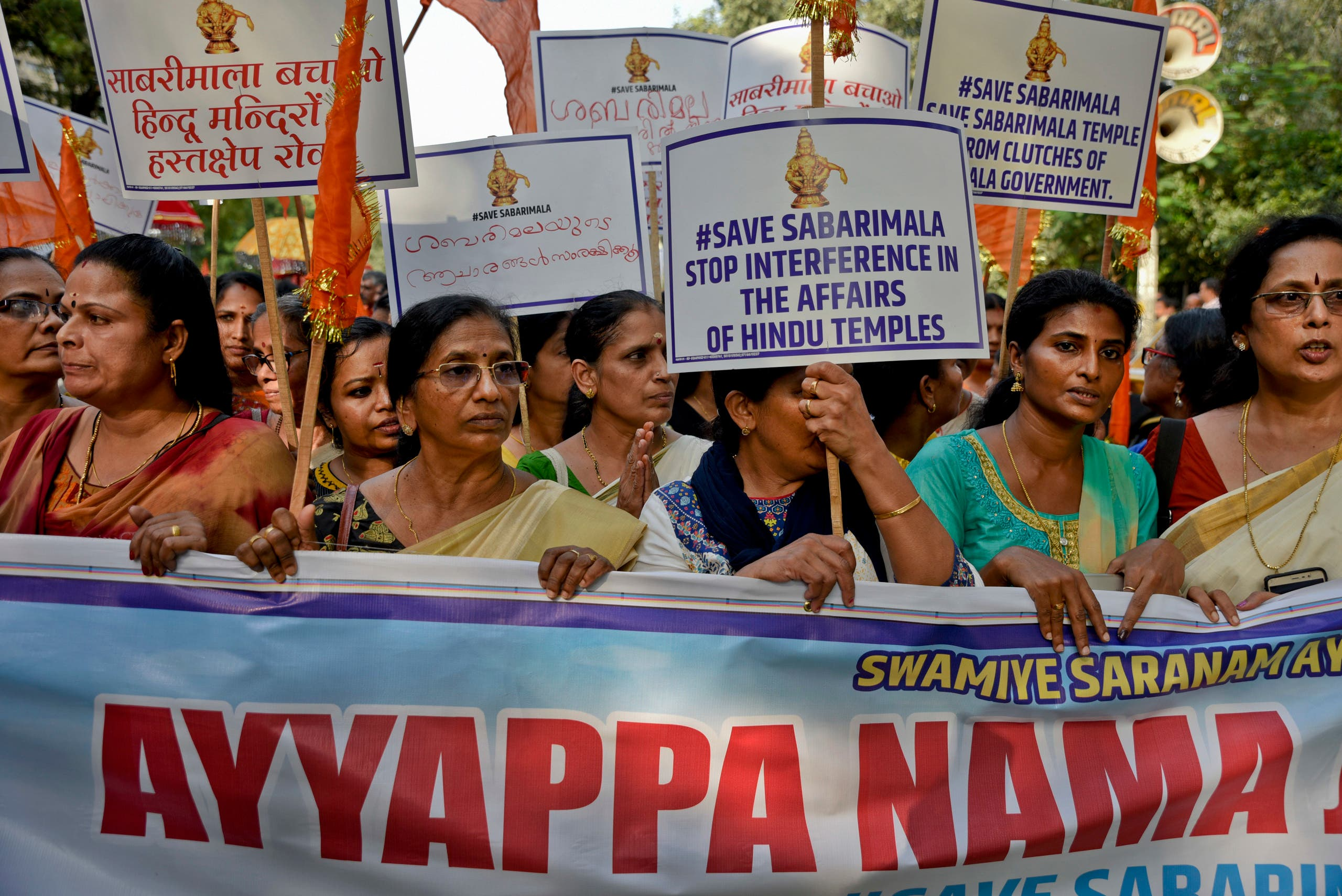 Indian Hindu women hold placards and chant religious hymns worshipping Lord Ayyappa, the deity of Sabarimala temple, as they arrive for a protest against a recent Supreme Court verdict in New Delhi, India. (AP)