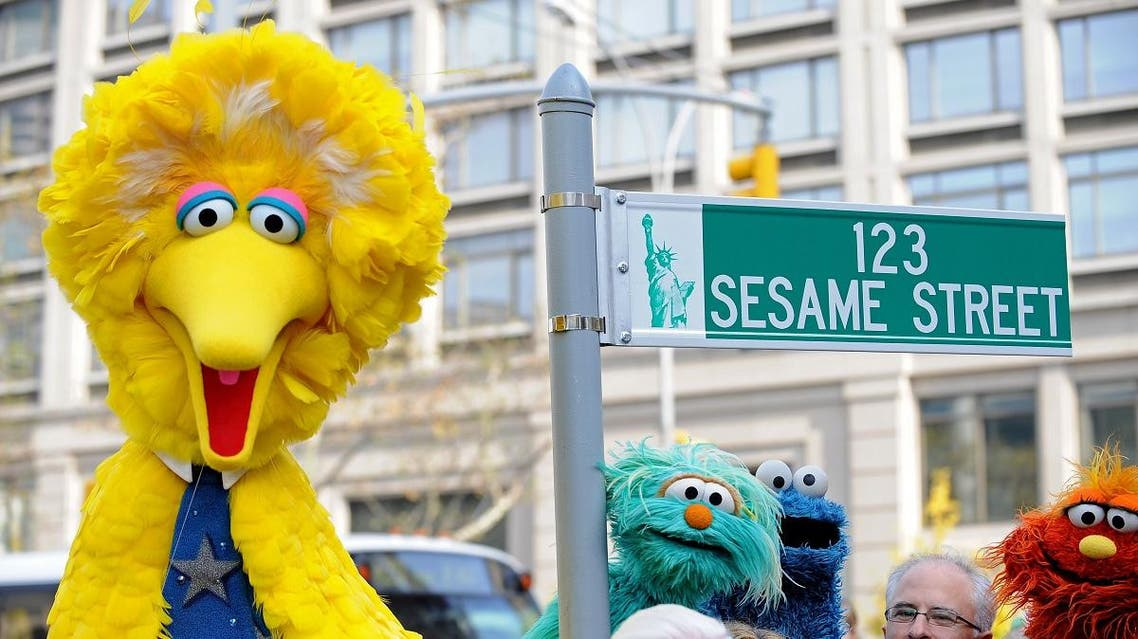 Big Bird (L) and other Sesame Street puppet charactors pose next to a temporarty street sign at West 64th Street and Broadway. (AFP)