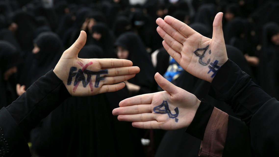 """Iranian protesters show their hands with writing in Persian that reads, """"No to FATF,"""" to protest the passage of a bill in Tehran on Oct. 7, 2018. (AP)"""