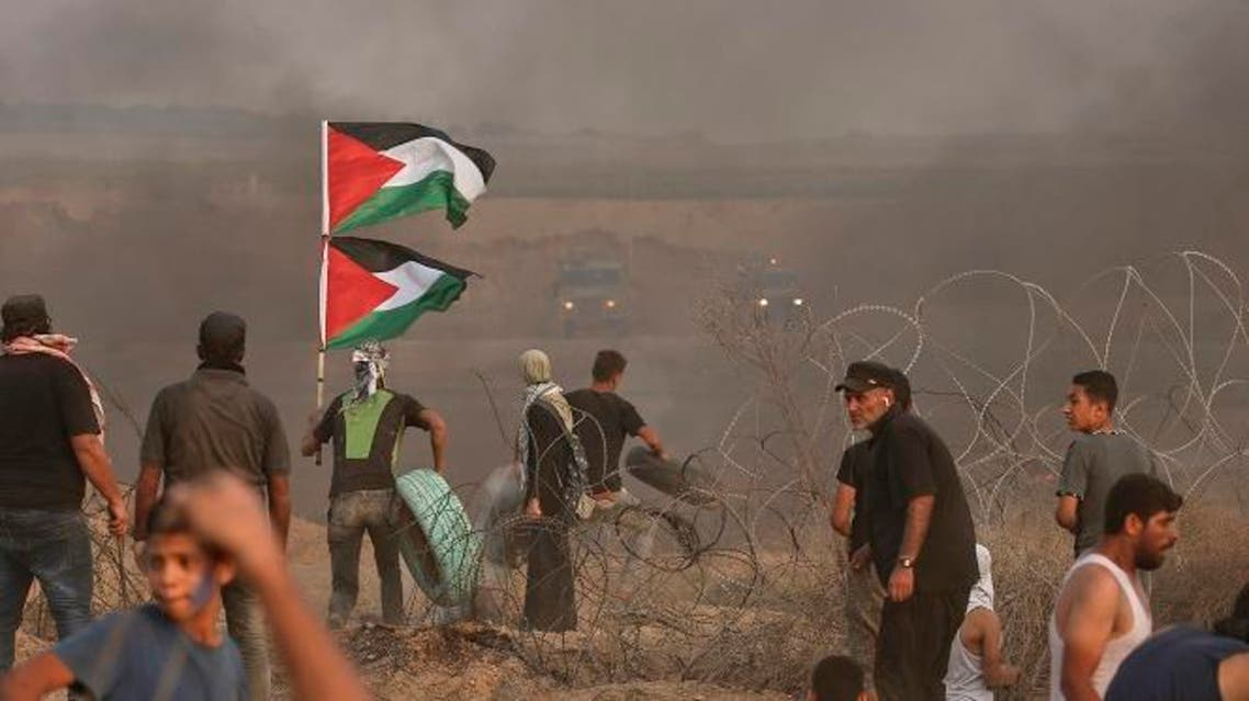A Palestinian protester carries his national flag and tyres to burn during a demonstration near the border with Israel, east of Gaza City, on October 19, 2018. (AFP)
