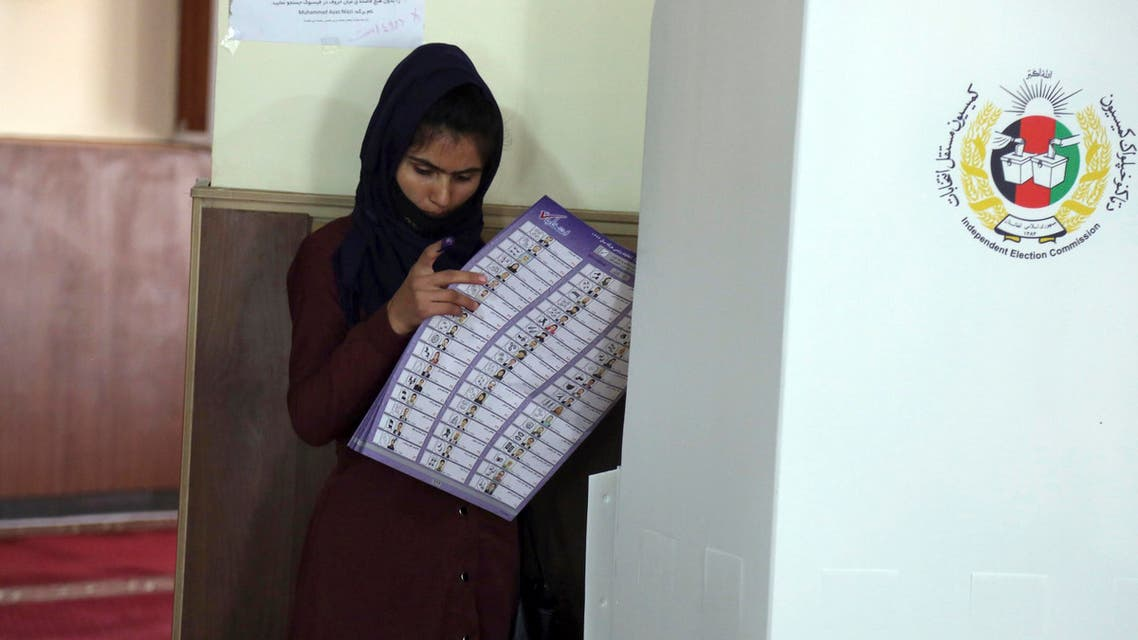 An Afghan woman searches for her candidate's name at a polling station during the Parliamentary elections in Kabul, Afghanistan, Saturday, Oct. 20, 2018. (AP)