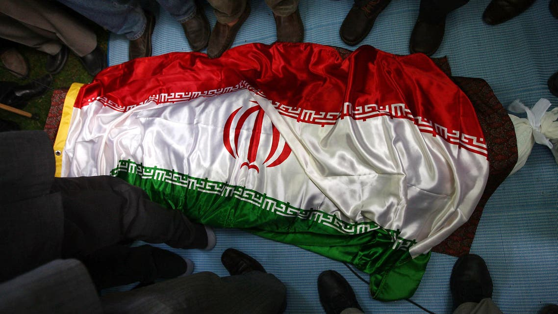 Mourners stand around the body of veteran Iranian opposition figure Ezatollah Sahabi draped in his national flag during his funeral in Lavasan on June 1, 2011. (AFP)