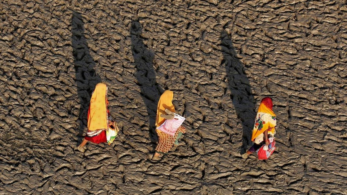 Women walk on the muddy banks of the Ganges river after taking a holy dip, in Allahabad. (Reuters)