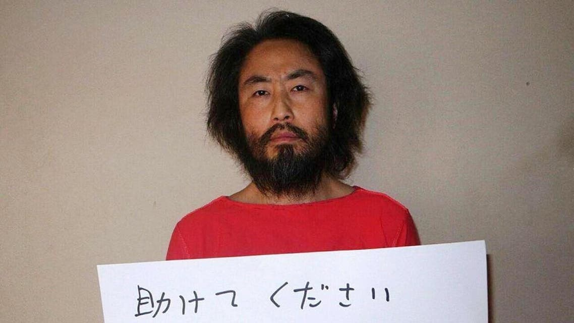 Photo shows Japanese freelance journalist Jumpei Yasuda holding a piece of paper with a handwritten message in Japanese. (AFP)