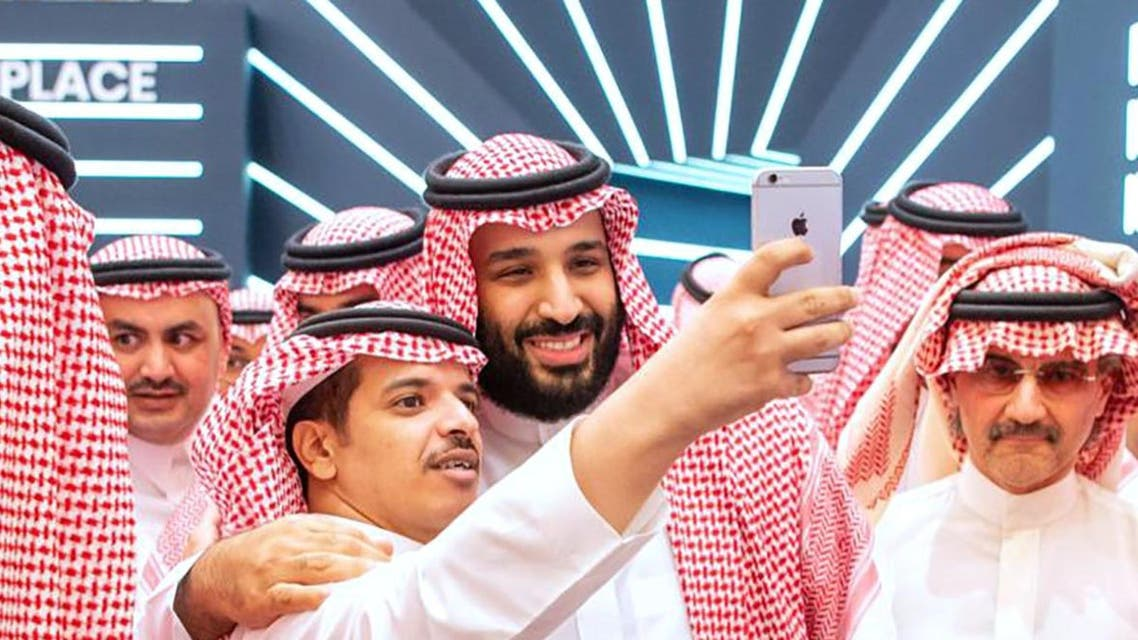 A handout picture provided by the Saudi Royal Palace on October 23, 2018 shows Saudi Crown Prince Mohammed bin Salman (L) posing for a selfie. (AFP)
