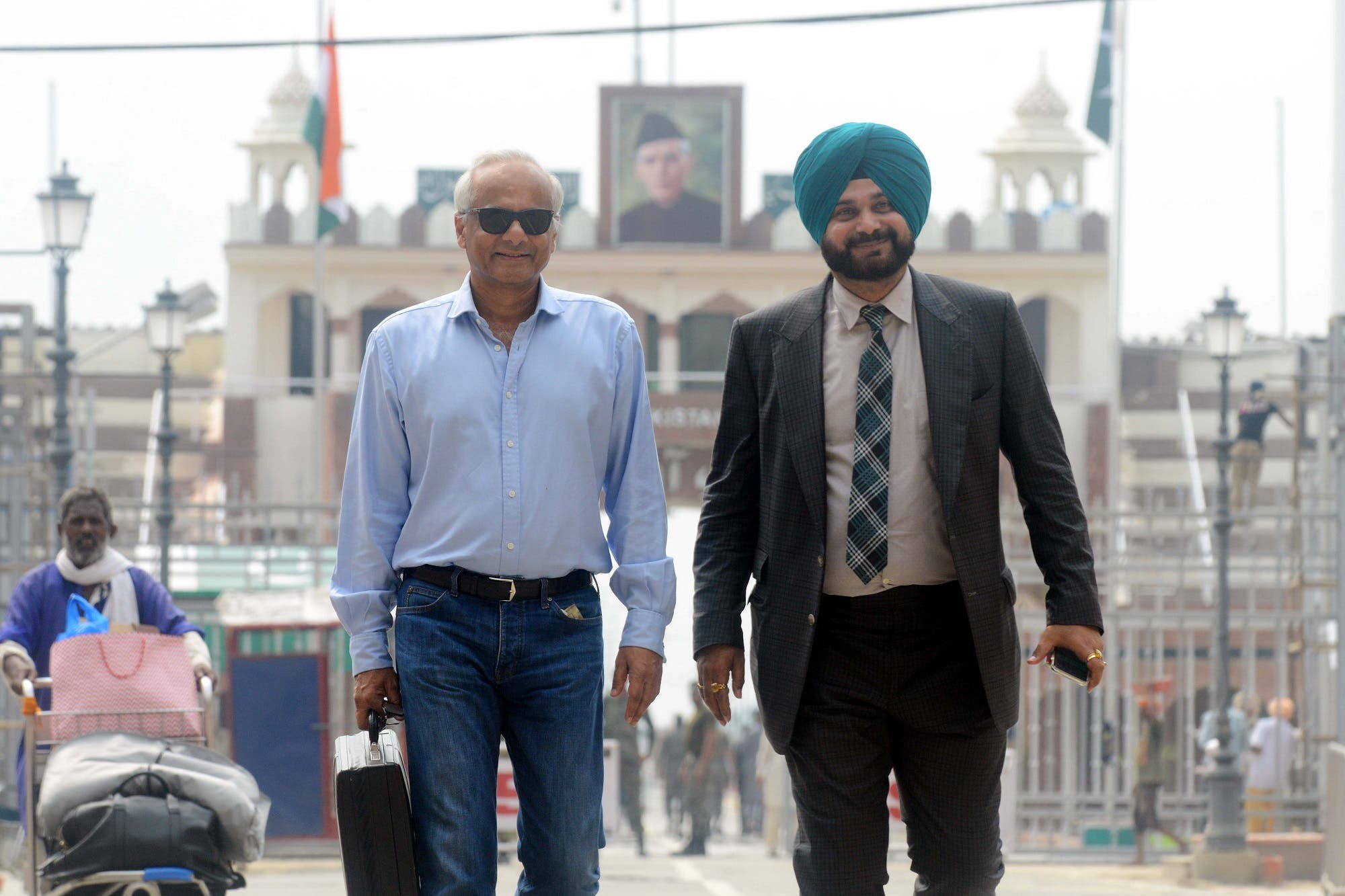 Navjot Singh Sidhu, and Vikram Singh Mehta (L), a friend of Pakistani Prime Minister Imran Khan, cross the India-Pakistan border in Wagah, on August 19, 2018. (AFP)