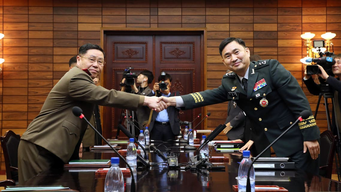 This handout photo taken on October 26, 2018 and provided by the South Korean Defence Ministry shows South Korea's chief delegate Major General Kim Do-gyun (R) shaking hands with his North Korean counterpart An Ik San (L) during their general-level military talks at the North side of the truce village of Panmunjom in the Demilitarized Zone (DMZ) dividing the two Koreas. The two Koreas agreed to remove 11 guard posts along the heavily-fortified border next month with a goal to possibly remove all guard posts in the future, senior military officials said on October 26.
