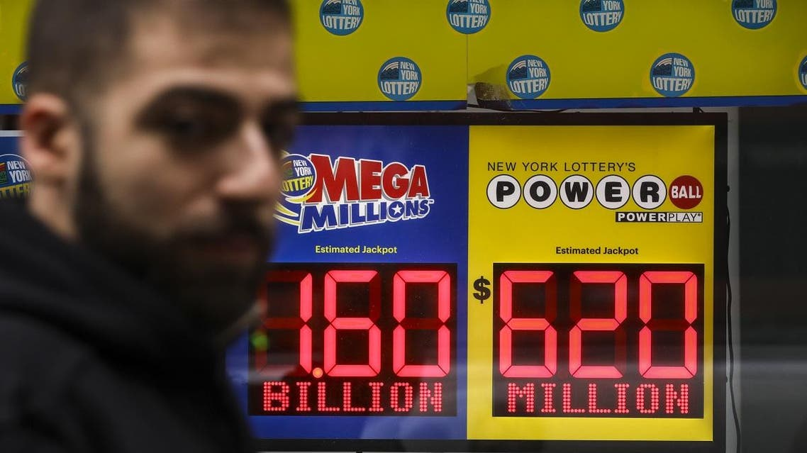 A man walks past advertisements for the Mega Millions and Powerball lottery hanging on a window of the New York Lottery Customer Service Center. (AFP)