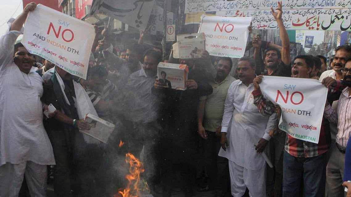 Pakistani electronic market traders chant slogans while they burn the decoders for Indian satellite TV channels during a protest in Lahore. (AP)