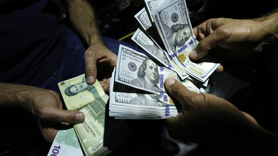 A man exchanges Iranian Rials against US Dollars at an exchange shop in Tehran on August 8, 2018. (AFP)