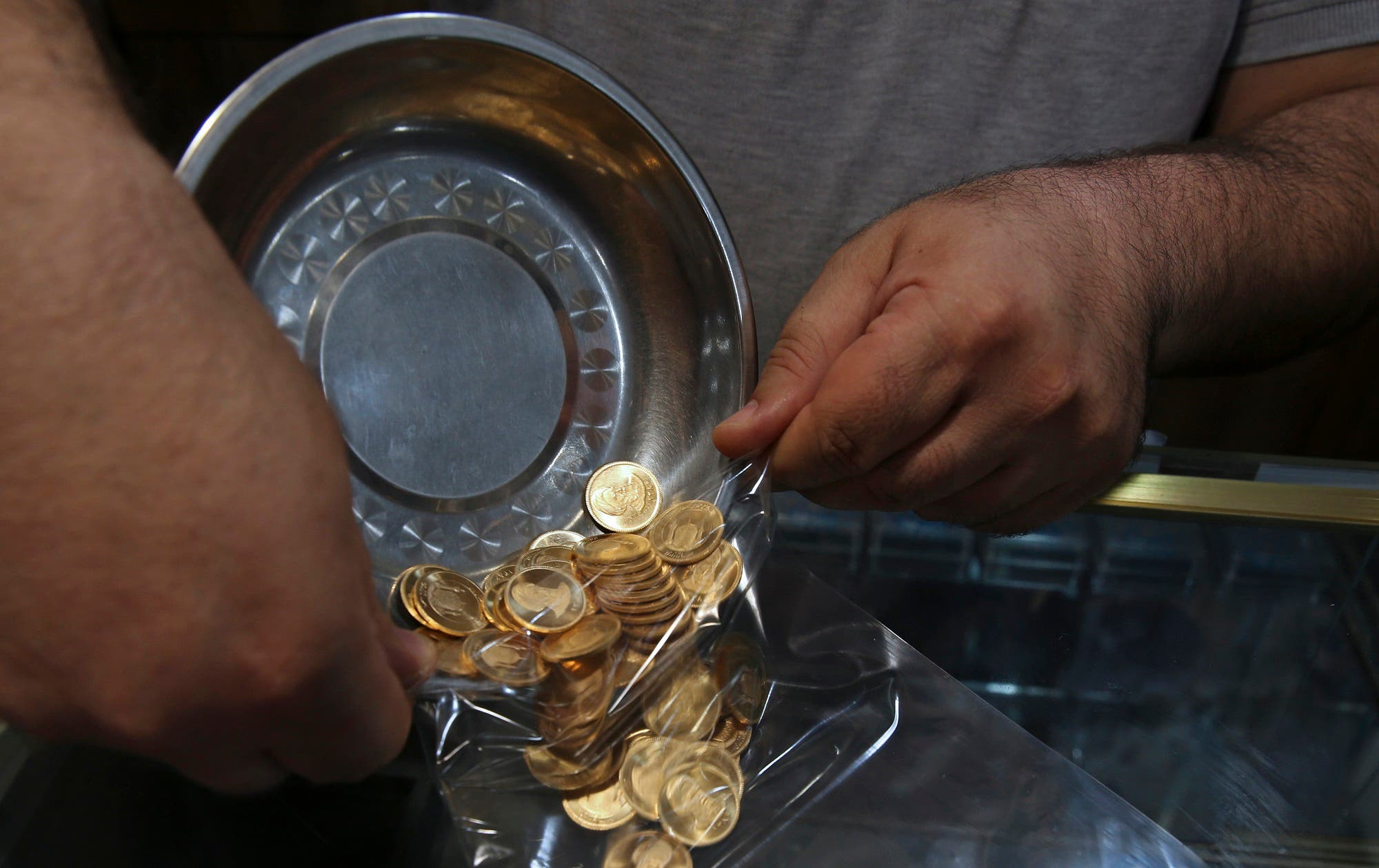 An Iranian goldsmith counts gold coins in Grand Bazaar, which has seen customers buying gold as a hedge against falling rial, in Tehran, on Aug. 12, 2018. (AP)