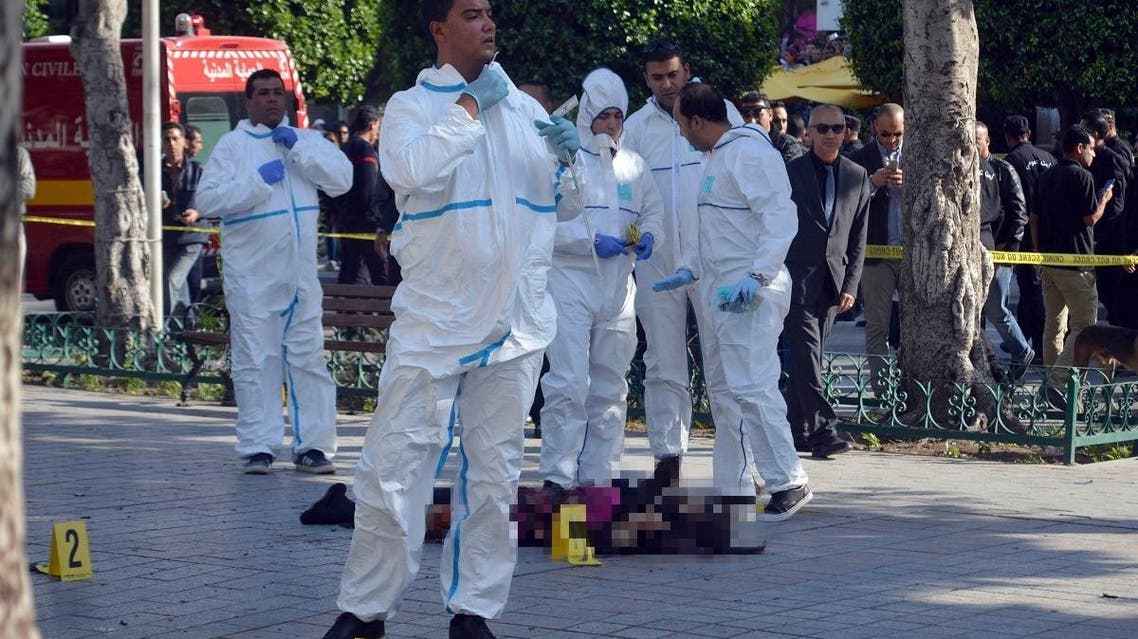Tunisian forensic experts stand around the lifeless body of a suicide bomber after she blew herself on the Habib Bourguiba avenue in Tunis. (AP)