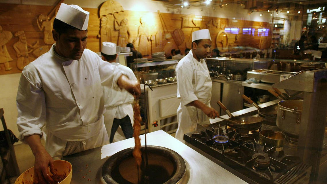 Cooks work in the kitchen of a curry house near Brick Lane in east London on Feb. 13, 2008. (File photo: AP)