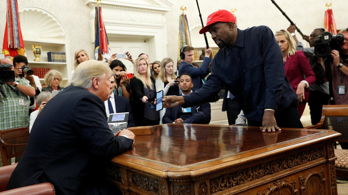 Rapper Kanye West shows President Donald Trump his mobile phone during a meeting in the Oval Office at the White House in Washington, U.S., October 11, 2018. REUTERS/Kevin Lamarque