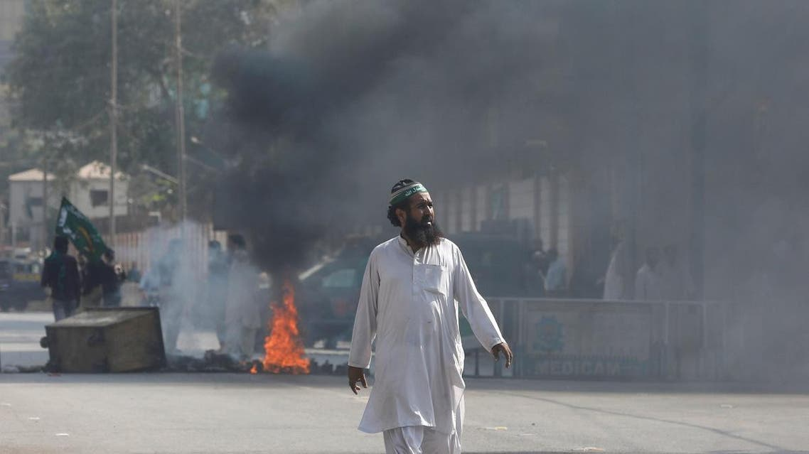 A supporter of the Tehrik-e-Labaik Pakistan (TLP) Islamist political party walks as supporters set ablaze tyres to block a road in Karachi. (Reuters)