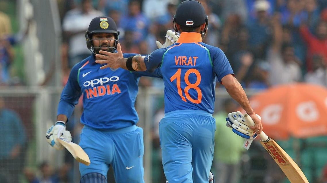 Indian batsman Rohit Sharma and captain Virat Kohli (R) celebrate their team's victory during the fifth ODI match against and West Indies in Thiruvananthapuram on November 1, 2018. (AFP)