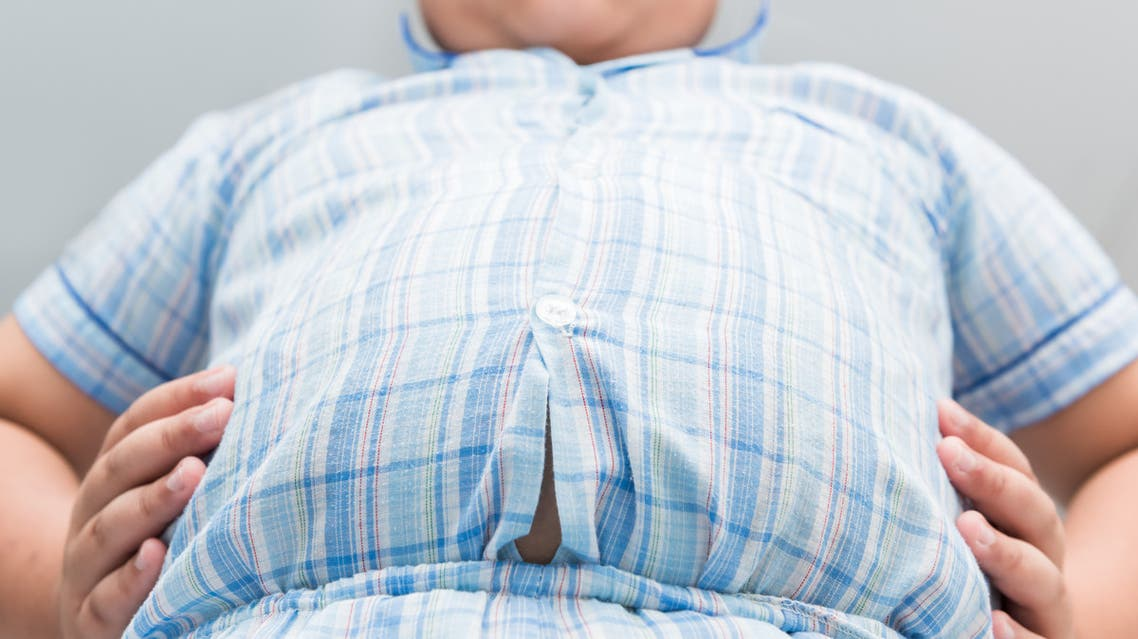 Obese fat boy overweight. Tight shirt of pajamas - Stock image