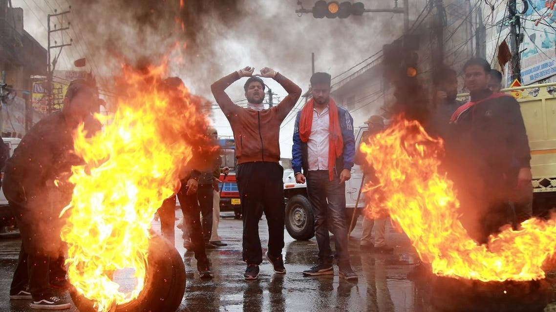 Demonstrators shout slogans next to burning tyres during a protest against the killing of a leader of India's ruling Bharatiya Janata Party's (BJP), and his brother by unidentified gunmen in Kishtwar town, in Jammu. (Reuters)