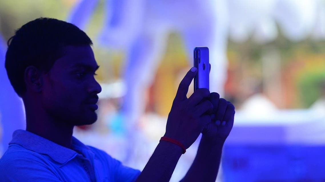 an Indian man takes a photo from his smartphone at a Durga Puja pandal in Allahabad. (AFP)