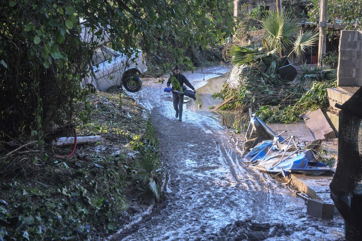 People pass on November 4, 2018 by damages on a flooded road near a house where nine people of the same family died after a small river burst its banks in Casteldaccia near Palermo on the southern Italian island of Sicily. Rescue services said the bodies of the family, including children aged one, three and 15, were found in their house and a man was found separately in his car while two other people are missing, they said, as Italy grapples with fierce storms which have already claimed at least 20 lives this week.