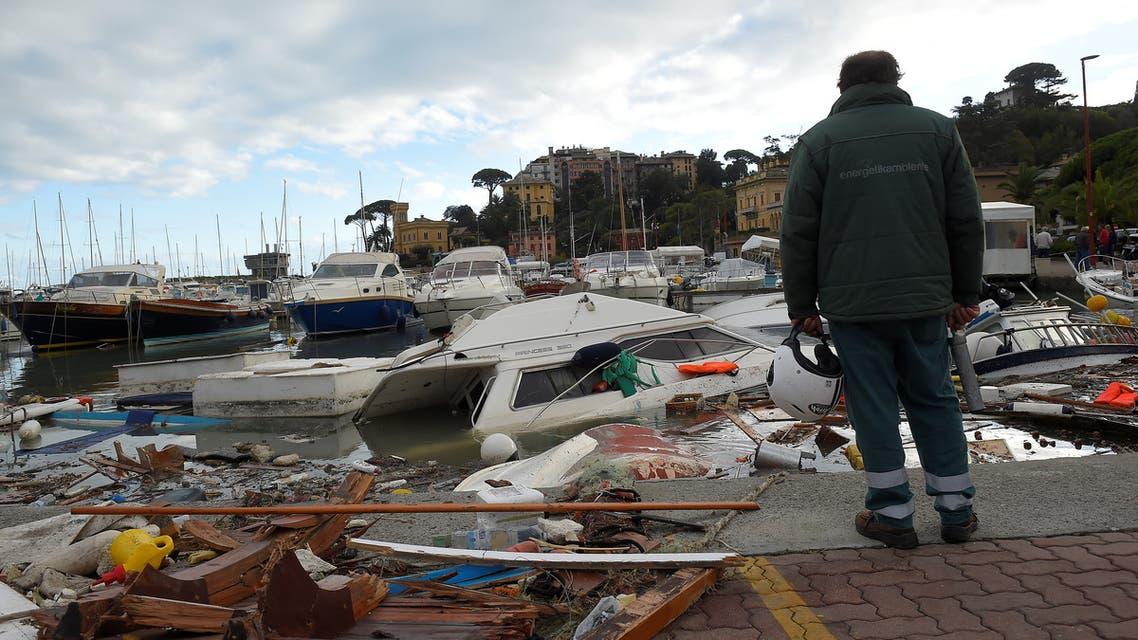 رجل ينظر إلى يخوت لحقت بها أضرار بعدما ضربت الأمطار الغزيرة والعواصف راباللو في إيطاليا