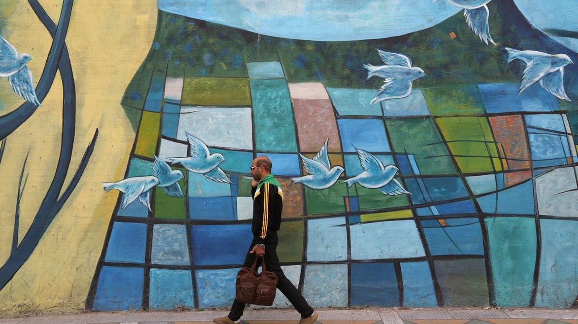 An Iranian man walks past colorful walls in Tehran on November 5, 2018. (AFP)